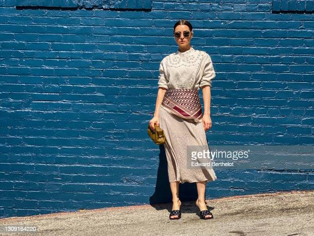Julia Comil wears a hair clip, sunglasses, a beige eyelet blouse in linen by Carven, a beige Midi skirt by Carven, a Dior silk scarf with printed...