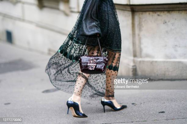 Julia Comil wears a Longchamp black and green dress with mesh, lace and puff sleeves, a leather crocodile pattern Longchamp bag, a brown Sandro...