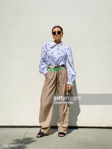 Julia Comil wears a Peter Pan collar blouse with puffy sleeves swallow-print in organic cotton by Munthe, beige silk track pants with drawstrings by...