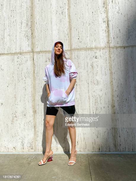 Julia Comil wears a pink and white tie-dye hoodie sweater from Baja East x Kevin Murphy, a fringed rhinestone black faux leather bandana scarf from...