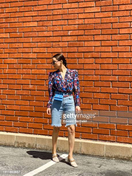 Julia Comil wears a retro floral printed draped top / shirt with padded shoulders by Iro Paris, 90's high rise loose fit Bermuda denim Shorts by...