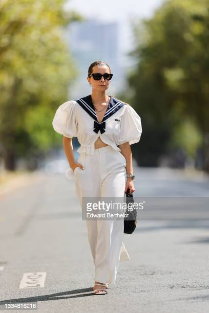 Julia Comil wears a white cropped blouse sailor with bow and puffed sleeves by Miu Miu, high waisted white palazzo pants, white sandals from By Far,...