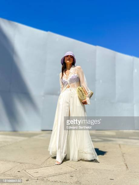 Julia Comil wears a White Tulle shirt dress by Selezza London, high waisted oversized white pants by Selezza London, a mauve pale purple lilac...
