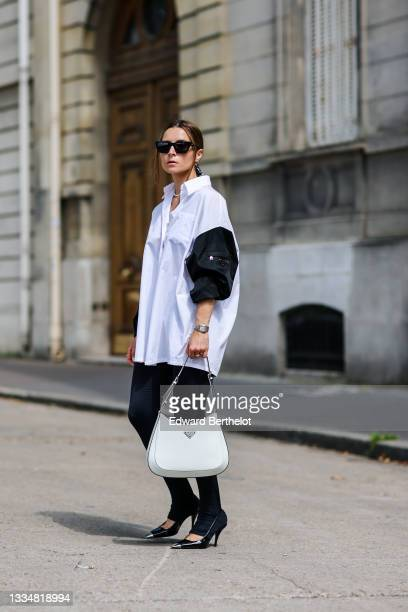 Julia Comil wears an oversized cotton white and black shirt with triangle Prada logo and zipped by Prada, black leggings, a Cleo white patent leather...