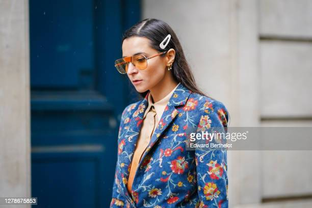 Julia Comil wears Ferragamo sunglasses, a hair brooch, a beige shirt, a floral print blue and colored blazer jacket with brown leather cuffs, outside...
