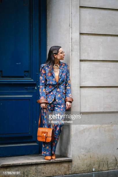 Julia Comil wears Ferragamo sunglasses, a hair brooch, a beige shirt, a floral print blue and colored blazer jacket with brown leather cuffs, suit...