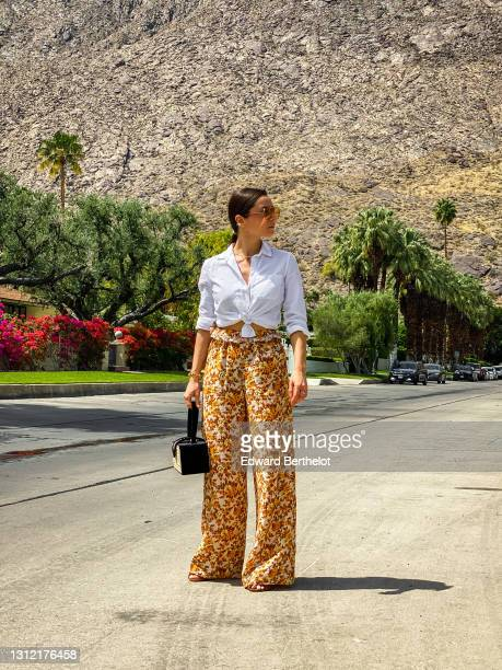 Julia Comil wears floral print flared flowy orange and brown palazzo pants by Jonathan Simkhai, a white linen shirt by Sezane, sustainable mules...