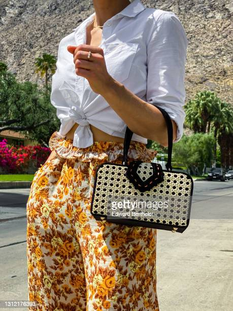 Julia Comil wears floral print flowy orange and brown palazzo pants by Jonathan Simkhai, a white linen shirt by Sezane, a vintage inspired cane box...