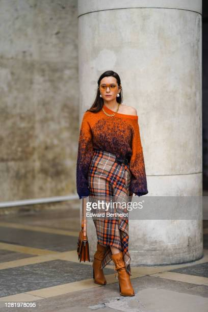 Julia Comil wears orange clear sunglasses, pearl earrings, a golden necklace, a one shoulder oversized wool orange and blue pullover with flared long...