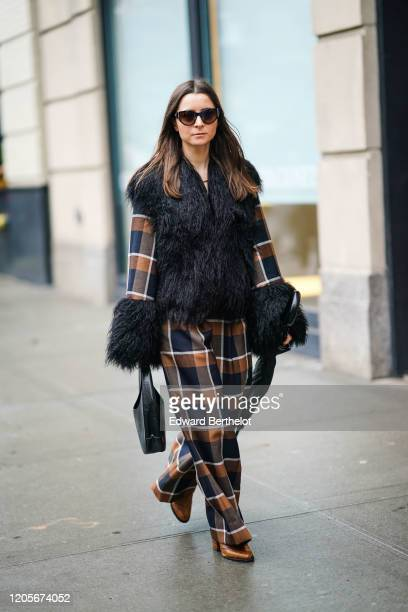 Julia Comil wears sunglasses a black fluffy faux fur jacket brown and black checked flared pants brown leather shoes a bag during New York Fashion...