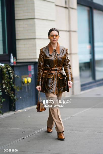 Julia Comil wears sunglasses a brown leather jacket light brown pants leather shoes a bag during New York Fashion Week Fall Winter 2020 on February...