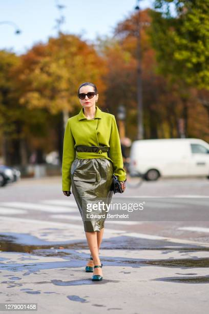 Julia Comil wears sunglasses, a green jacket, a dark green shiny pvc skirt, a small leather bag, shoes, outside Chanel, during Paris Fashion Week -...