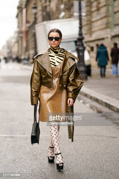 Julia Comil wears sunglasses, earrings, a gold-tone and black tiger pattern turtleneck, a light brown leather strappy dress, a bronze-tone leather...