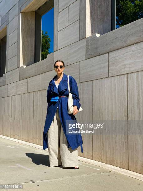 Julia Comil wears sunglasses from Chanel, a blue spring trench coat from Nehera, beige linen flared pants from Nehera, a large triangle-shaped white...