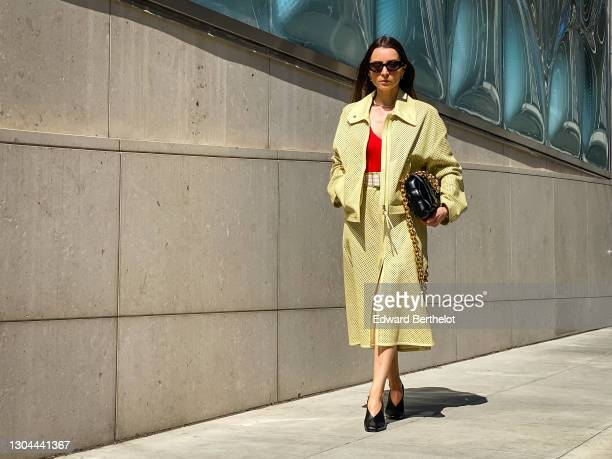 Julia Comil wears sunglasses from Ferragamo, a yellow perforated leather jacket in lime from Ferragamo, a red low-neck bodysuit from Ferragamo, a...