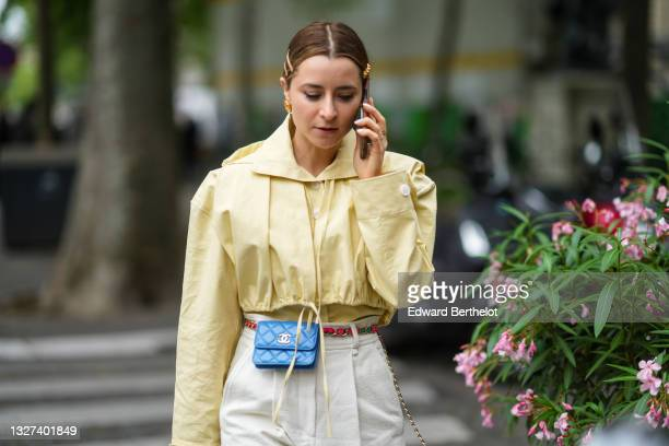 Julia Comil wears sunglasses, gold hair clips, gold earrings, a pale yellow shirt, a matching pale yellow adjustable hoodie vest / short jacket, a...