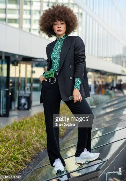Julia Dalia is seen wearing a black suit jacket by Acne Studios a Lacoste green longsleeve top Flippa K trousers with a Calvin Klein belt a Jacquemus...