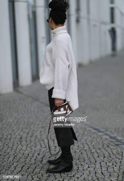 Julia Dalia wearing Samsoe Samsoe beige sweater, Loewe brown puzzle bag, Tiger of Sweden skirt and Gia Couture boots during the Mercedes-Benz Fashion...