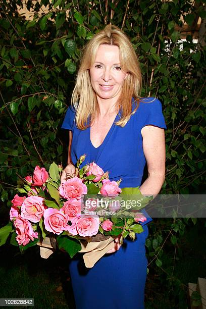 Julia Delves Broughton wearing Alexander McQueen poses with 'Alexander's Issie' roses while attending the Press preview at the Hampton Court Palace...