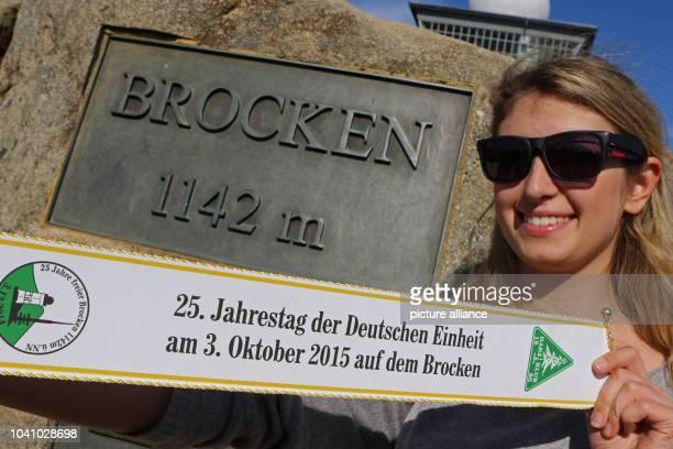 Julia Druemmer poses with a banner that reads '25 Jahrestag der Deutschen Einheit am 3 Oktober 2015 auf dem Brocken' on Brocken mountain Germany 03...