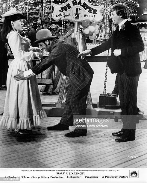 Julia Foster and Tommy Steele are shocked as man pads her down to guess her weight in a scene from the film 'Half A Sixpence' 1967