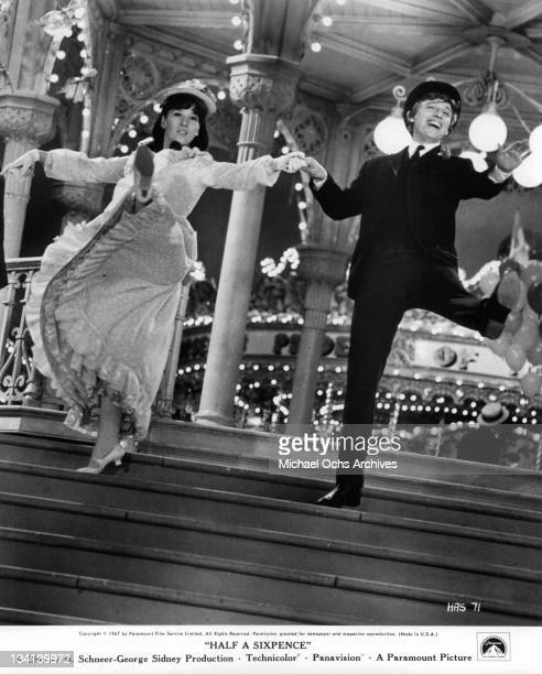 Julia Foster and Tommy Steele dancing down steps in a scene from the film 'Half A Sixpence', 1967.