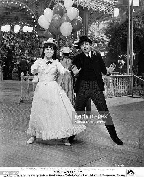 Julia Foster and Tommy Steele putting their hands out in a scene from the film 'Half A Sixpence', 1967.