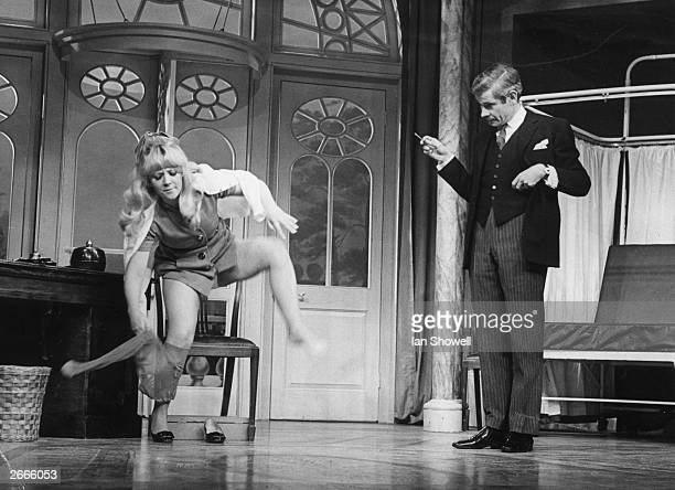 Julia Foster as Geraldine Barclay removes her tights in front of Stanley Baxter as Dr Prentice during a dress rehearsal of 'What the Butler Saw' by...