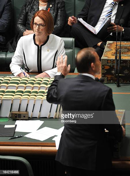 Julia Gillard Australia's prime minister left reacts as Tony Abbott Australia's opposition leader speaks during question time at Parliament House in...