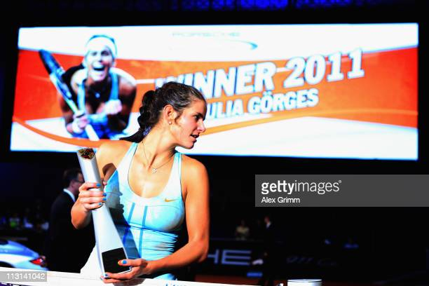 Julia Goerges of Germany poses for photographers after defeating Caroline Wozniacki of Denmark in the Final match at the Porsche Tennis Grand Prix at...