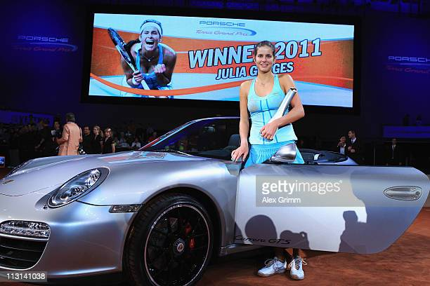 Julia Goerges of Germany poses in her new Porsche Carrera 911 GTS after defeating Caroline Woznjacki of Denmark in the Final match at the Porsche...
