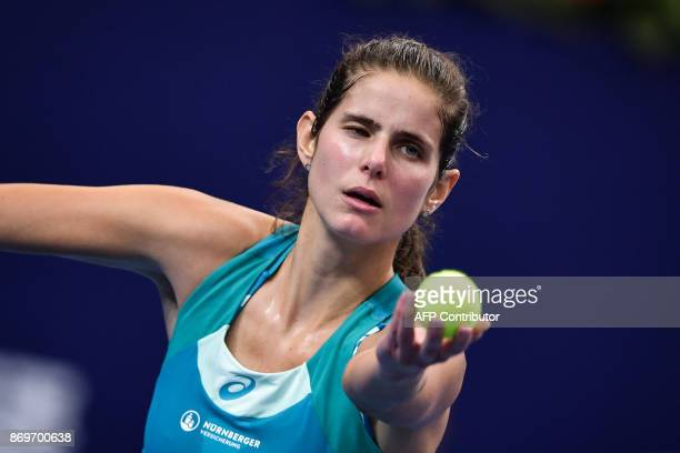 Julia Goerges of Germany serves to Kristina Mladenovic of France during their women's singles match at the Zhuhai Elite Trophy tennis tournament in...