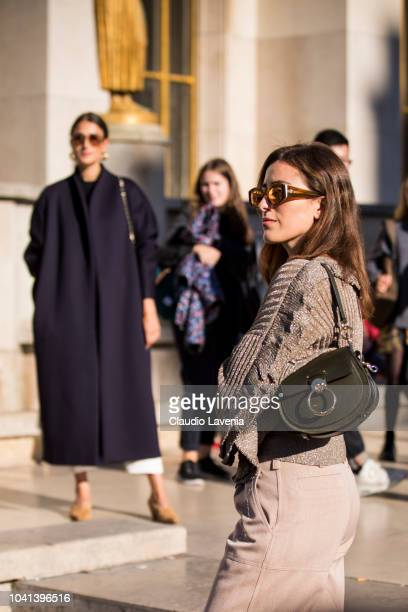 Julia Haghjoo and Sylvia Haghjoo wearing a blue coat white trousers blue Chanel bag and tan shoes and taupe sweater taupe trousers and black bag are...