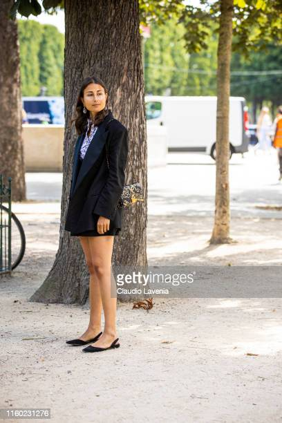 Julia Haghjoo, wearing a black and white printed top, black blazer, black short, black shoes and black and gold printed Chanel bag, is seen outside...