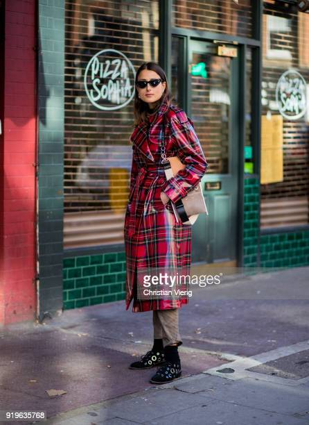 Julia Haghjoo wearing red black plaid Burberry coat seen outside JW Anderson during London Fashion Week February 2018 on February 17 2018 in London...