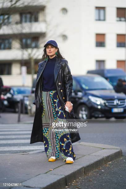 Julia Haghjoo wears a blue cap, a long black leather coat, a navy blue pullover, Lacoste flared pants with printed geometric patterns, earrings,...