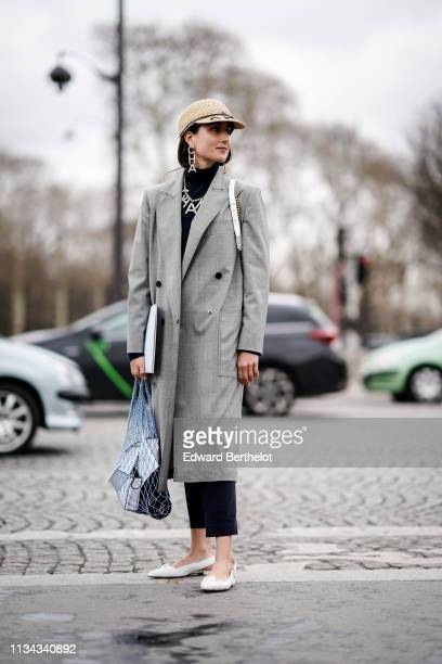 Julia Haghjoo wears a straw Chanel cap Chanel strass earrings a Chanel strass necklace a grey Prince of Wales check coat black crop pants white...
