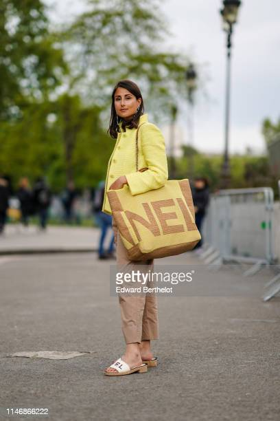 Julia Haghjoo wears a yellow Chanel tweed jacket, a large Chanel brown and yellow bag, Chanel earrings, beige pants, Chanel sandals, a white top,...