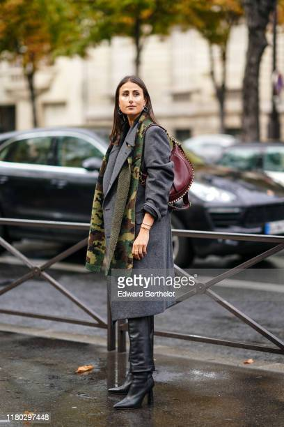 Julia Haghjoo wears earrings, bracelets, a khaki and yellow camouflage scarf, a grey oversized coat with shoulder pads, a burgundy studded bag, black...