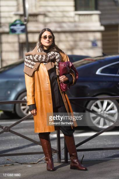 Julia Haghjoo wears sunglasses, a brown leather coat, a purple leather bag, a wool pullover with printed patterns, black pants, leather boots,...