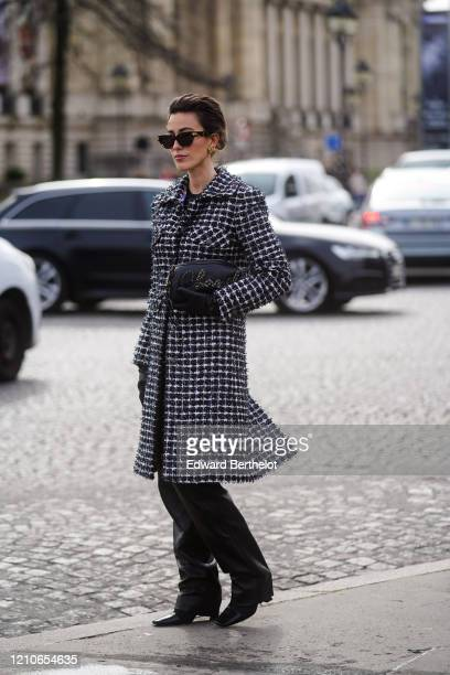 Julia Haghjoo wears sunglasses, a Chanel bag, leather gloves, a black and white tweed long coat, black leather pants, pointy shoes, outside Chanel,...
