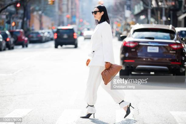 Julia Hayek is seen wearing white blazer pants and black laced heels Asos brown bag and gloves Zara Celine sunglasses during New York Fashion Week...