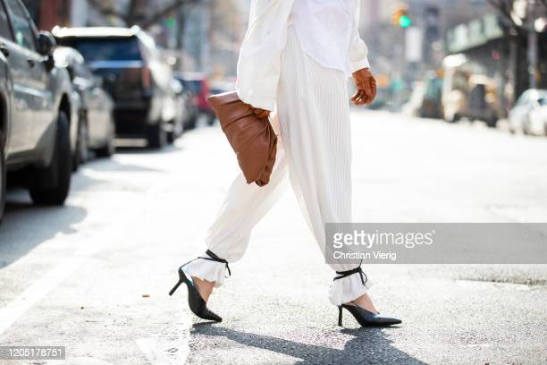 Julia Hayek is seen wearing white blazer pants and black laced heels Asos brown bag and gloves Zara during New York Fashion Week Fall / Winter on...