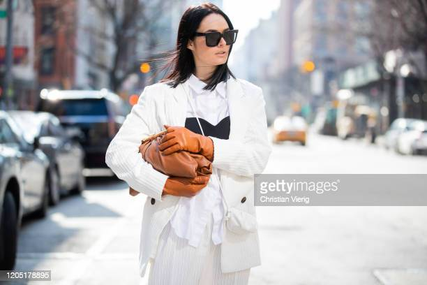 Julia Hayek is seen wearing white blazer pants Asos brown bag and gloves Zara Celine sunglasses during New York Fashion Week Fall / Winter on...