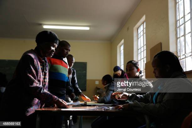 Julia Kgatle has her ID checked before voting at the Orlando West Voting Station at the Orlando West Secondary School during the 2014 South African...