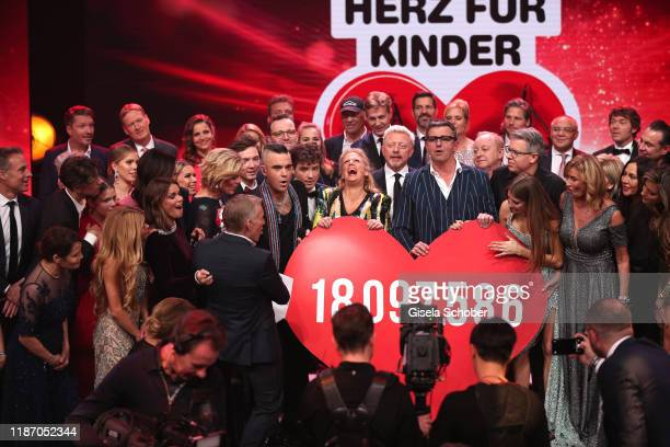 Julia Kloeckner Johannes B Kerner Robbie Williams Barbara Schoeneberger Boris Becker Hans Sigl Cathy Hummels with the final donation check during the...