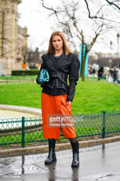 "Julia Kuczynska ""Maffashion"" wears a black oversized jacket with puff sleeves, a metallic chain necklace, a corset, a blue shiny Bottega Veneta The..."