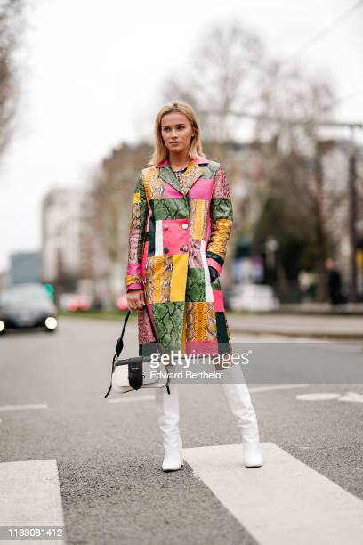 Julia Kuczynska Maffashion wears a multicolor snake print vinyl trench coat white boots a Prada bag outside Nina Ricci during Paris Fashion Week...