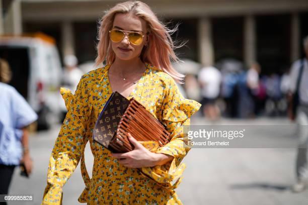 Julia Kuczynska Maffashion wears a yellow floral print dress Gucci sneakers shoes sunglasses and a Vuitton clutch outside the Louis Vuitton show...
