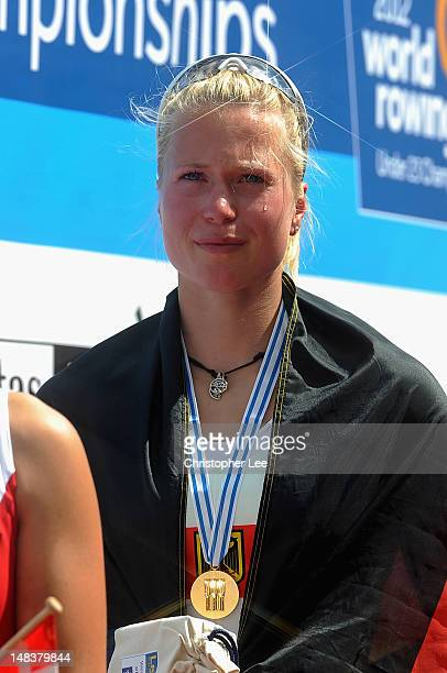 Julia Lier of Germany cries as she stands for the German National anthem after she wins gold in the Women's Single Sculls Final during Day 5 of the...